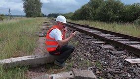 Trabalhador Railway no Walkietalkie que senta-se perto dos trilhos vídeos de arquivo