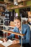 Trabalhador seguro que sorri ao ligar papéis fotografia de stock