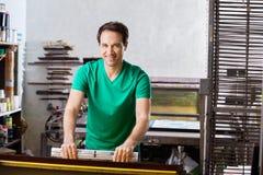 Trabalhador seguro que usa o rodo de borracha na fábrica de papel Foto de Stock Royalty Free