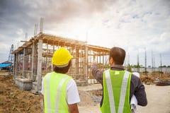 Trabalhadores asiáticos do coordenador de construção do homem de negócio no terreno de construção Imagem de Stock