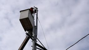 Trabalhadores bondes em Telehandler com a cubeta que instala fios de tensão alta filme