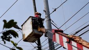 Trabalhadores bondes em Telehandler com a cubeta que instala fios de tensão alta video estoque
