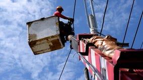 Trabalhadores bondes em Telehandler com a cubeta que instala fios de tensão alta vídeos de arquivo