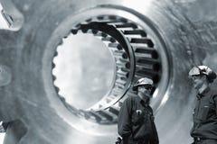 Trabalhadores com engrenagens e os eixos gigantes das rodas denteadas Imagens de Stock