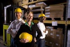 Trabalhadores com a saliência fêmea no armazém de armazenamento Fotos de Stock Royalty Free
