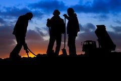 Trabalhadores da construção com o caminhão na silhueta do por do sol Fotografia de Stock