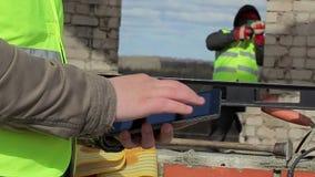Trabalhadores da construção com PC e broca da tabuleta na construção filme
