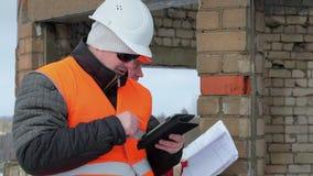 Trabalhadores da construção com PC e documentação da tabuleta video estoque