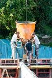 Trabalhadores da construção da construção no concreto de derramamento do canteiro de obras no formulário foto de stock