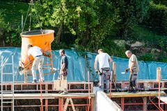 Trabalhadores da construção da construção no concreto de derramamento do canteiro de obras no formulário fotografia de stock