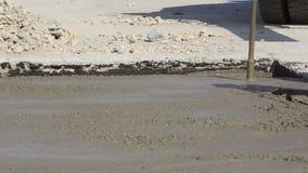 Trabalhadores da construção que comprimem o cimento líquido em uma construção da pista de decolagem video estoque