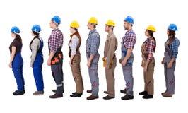 Trabalhadores da construção que estão na fila fotografia de stock