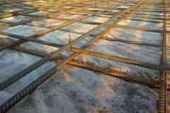 Trabalhadores da construção que fabricam a barra de aço do reforço no canteiro de obras foto de stock