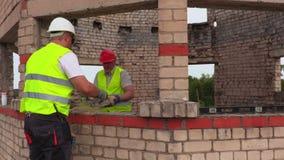 Trabalhadores da construção que jogam tijolos filme