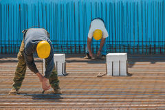 Trabalhadores da construção que ligam as barras de aço com fios Imagem de Stock Royalty Free