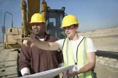 Trabalhadores da construção que olham o plano no local Foto de Stock Royalty Free