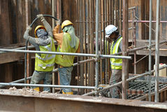 Trabalhadores da construção que usam o vibrador concreto para comprimir o concreto Imagens de Stock