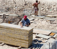 Trabalhadores da construção que fabricam o feixe à terra Imagem de Stock