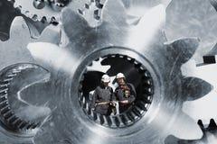 Trabalhadores da indústria dentro dos eixos gigantes das rodas denteadas fotos de stock royalty free