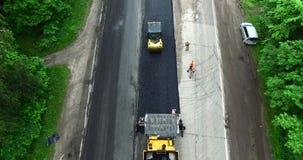 Trabalhadores de construção de estradas com máquina de pavimentação filme