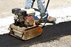 Trabalhadores de construção de estradas que espalham o asfalto imagem de stock