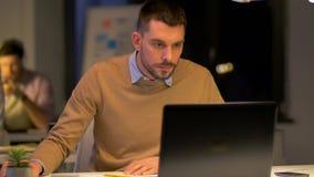 Trabalhadores de escritório com o portátil que trabalha na noite filme
