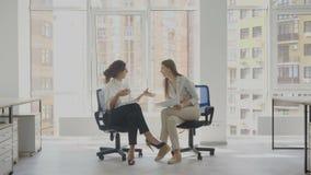 Trabalhadores de escritório, duas mulheres que sentam-se nas cadeiras falando, discutindo documentos de trabalho, os casos do ` s video estoque