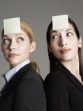 Trabalhadores de escritório fêmeas com notas pegajosas nas testas Fotos de Stock