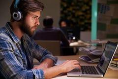 Trabalhadores de escritório nas mesas que trabalham tarde em portáteis imagens de stock royalty free