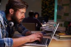 Trabalhadores de escritório nas mesas que trabalham tarde em portáteis foto de stock