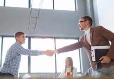 Trabalhadores de escritório que agitam as mãos em um fundo claro Reunião de negócio bem sucedida Conceito de uma comunicação foto de stock royalty free