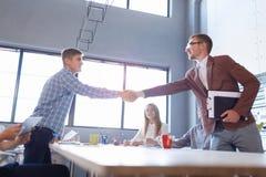 Trabalhadores de escritório que agitam as mãos em um fundo claro Reunião de negócio bem sucedida Conceito de uma comunicação fotografia de stock royalty free