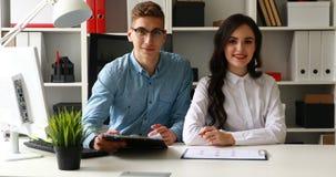 Trabalhadores de escritório que sentam-se na tabela e que sorriem na câmera