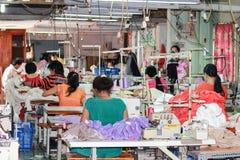Trabalhadores de matéria têxtil em uma fábrica pequena Fotos de Stock