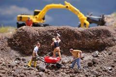 Trabalhadoresde MiniatureContruction que trabalham a pedra de levantamento usando a pá fotos de stock royalty free