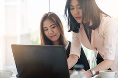 Trabalhadores de mulheres asiáticos novos que trabalham junto no escritório Imagens de Stock