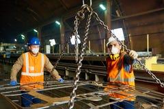 Trabalhadores de planta de aço que usam o feixe de levantamento imagem de stock
