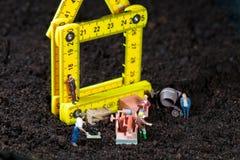 Trabalhadores diminutos que constroem uma casa Imagem de Stock