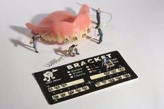 Trabalhadores diminutos que executam procedimentos dentais Escritório dental AR fotografia de stock