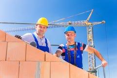 Trabalhadores do canteiro de obras que constroem a casa com guindaste Fotografia de Stock Royalty Free