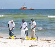 Trabalhadores do derramamento de petróleo que limpam a praia Imagens de Stock