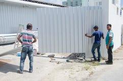 Trabalhadores do grupo que reparam portas Imagem de Stock Royalty Free