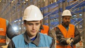 Trabalhadores do movimento lento na caminhada dos capacetes ao longo do armazém vídeos de arquivo