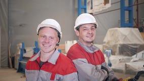 Trabalhadores do retrato que trabalham com um guindaste no armazém Sorriso olhando a câmera a produção de ventilação e filme