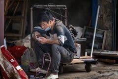 Trabalhadores emigrantes que olham telefones celulares ao descansar fotografia de stock royalty free