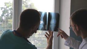 Trabalhadores médicos em cópias de vista e analizing do hospital do raio X O médico consulta um com o otro Mri masculino da opini vídeos de arquivo