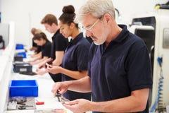Trabalhadores na fábrica de engenharia que verificam a qualidade componente fotos de stock
