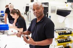 Trabalhadores na fábrica de engenharia que verificam a qualidade componente imagem de stock royalty free