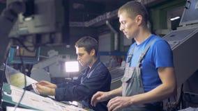 Trabalhadores na fábrica industrial que trabalha com écran sensível do computador video estoque