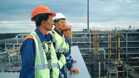 Trabalhadores na planta de produção como a equipe que discute, cena industrial no fundo vídeos de arquivo